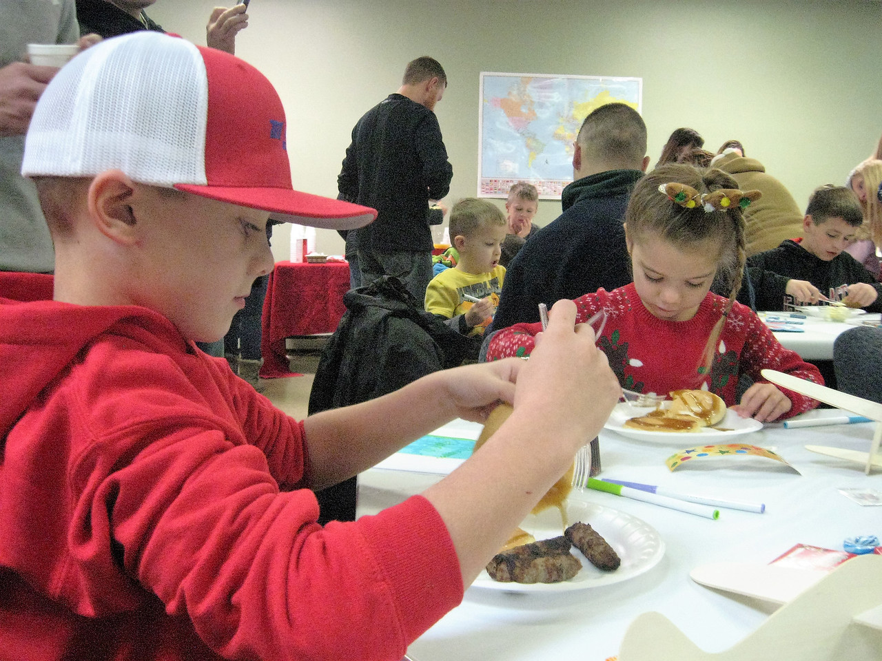 BOB SANDRICK / GAZETTE Carter Moore, 8, left, and his sister Riley Moore, 6, enjoyed crafts and breakfast before Santa's arrival Saturday at Wadsworth Municipal Airport. They were with parents Scott and Trudee Moore. The family is from New Franklin.