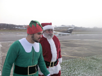 BOB SANDRICK / GAZETTE Santa walks from his plane with the Wadsworth Municipal Airport Chief Elf Nick Belluardo.