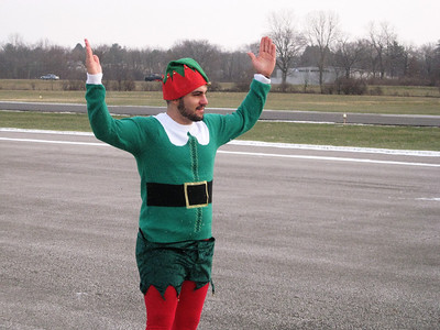 BOB SANDRICK / GAZETTE Chief Elf Nick Belluardo signaled Santa's plane onto the runway Saturday morning at Wadsworth Municipal Airport.