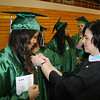JOHN KLINE | THE GOSHEN NEWS<br /> Concord High School Assistant Principal Denise Tahara, right, assists graduating senior Barbara Sebastian with her gown before the kickoff of the 2013 graduation ceremony at the high school Friday evening.