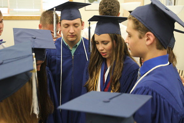 JULIE CROTHERS BEER | THE GOSHEN NEWS<br /> Class president and valedictorian Bethany Mullet offers a short prayer before the graduation ceremony begins Friday at Clinton Christian School. At her left is fellow graduate Austin Miller and to the right is Keidrick Miller.