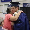 JULIE CROTHERS BEER | THE GOSHEN NEWS<br /> Clinton Christian School graduate Austin Miller hugs his mom while presenting her with a rose during Friday's graduation ceremony.
