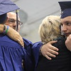 "JULIE CROTHERS BEER | THE GOSHEN NEWS<br /> Graduating seniors Austin Miller, left, and Keidrick Miller, right, hug Allen and Cindy Eash, the parents of former Clinton Christian School classmate Benjamin Eash during the graduation ceremony Friday at the school. Benji Eash died of cystic fibrosis when he was a freshman and was honored Friday with an ""in memoriam"" diploma."