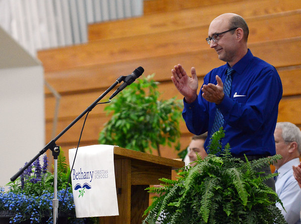 HALEY WARD | THE GOSHEN NEWS<br /> Head of school Tim Lehman claps while welcoming students and families during Bethany Christian High School's commencement on Sunday.