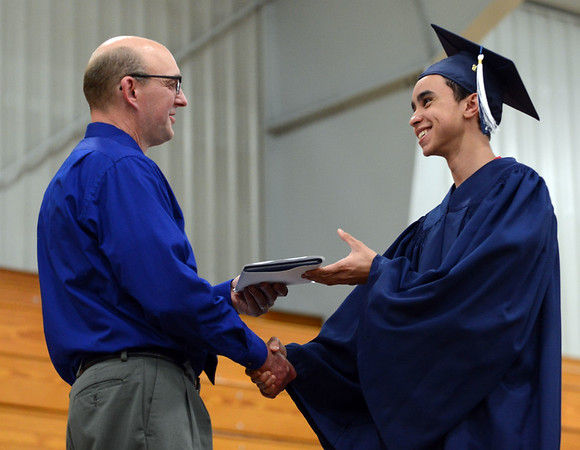 HALEY WARD | THE GOSHEN NEWS<br /> Head of school Tim Lehman hands Elijah Lora his diploma during Bethany Christian High School's commencement on Sunday.