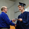HALEY WARD | THE GOSHEN NEWS<br /> Head of school Tim Lehman hands John Lapp his diploma during Bethany Christian High School's commencement on Sunday.