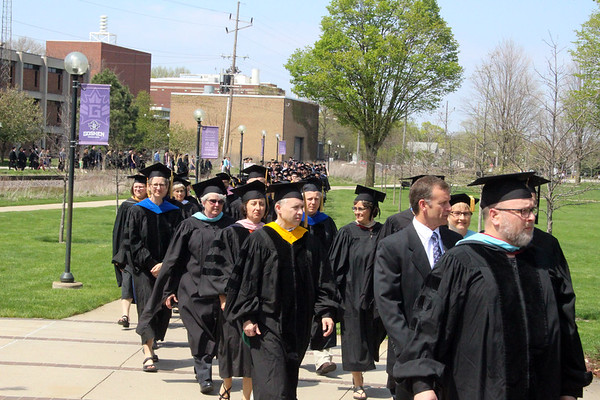 SHERRY VAN ARSDALL | THE GOSHEN NEWS<br /> Faculty of Goshen College lead the processional of the 118th Goshen College Commencement Sunday from the Union Building across campus to the Roman Gingerich Recreation-Fitness Center.