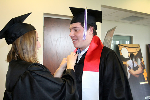 SHERRY VAN ARSDALL | THE GOSHEN NEWS<br /> At left, Kayla Riportella, Chicago, Ill., pins a green ribbon on the gown of Balazs Pirot, Hungary, before the processional of the 118th Goshen College Commencement Sunday. Riportella's major was English secondary education and will teach 10th grade at Wawasee High School in the fall. Pirot majored in accounting and information technology.