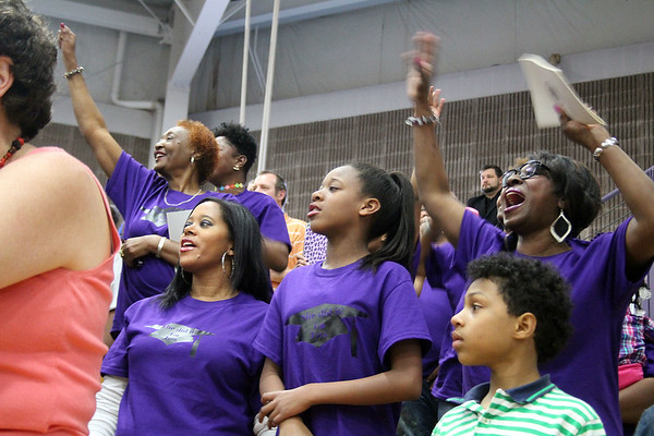 SHERRY VAN ARSDALL | THE GOSHEN NEWS<br /> Family members of Tyra Carver, Kalamazoo, Mich., cheer the graduate as she walks in the processional of the 118th Goshen College Commencement Sunday in the Roman Gingerich Recreation-Fitness Center.