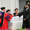 STEPHEN BROOKS | THE GOSHEN NEWS<br /> Goshen College graduating senior Dominique Bolden, right, shakes hands with GC President James Brenneman prior to receiving a placeholder diploma during Sunday's commencement ceremony.