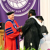SHERRY VAN ARSDALL | THE GOSHEN NEWS<br /> Zachary Gillis, Mishawaka, gets a handshake from President James Brenneman after receiving his hood for the master of art degree in intercultural leadership during the 118th Goshen College Commencement Sunday in the Roman Gingerich Recreation-Fitness Center.