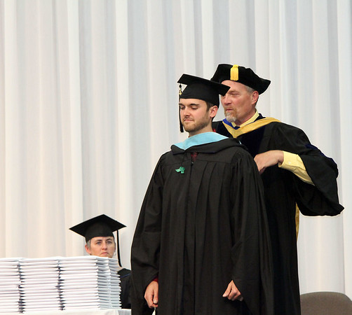 SHERRY VAN ARSDALL | THE GOSHEN NEWS<br /> Lee Renshaw, Richardson, Texas, received his hood for the master of art degree in environmental education during the 118th Goshen College Commencement Sunday in the Roman Gingerich Recreation-Fitness Center.