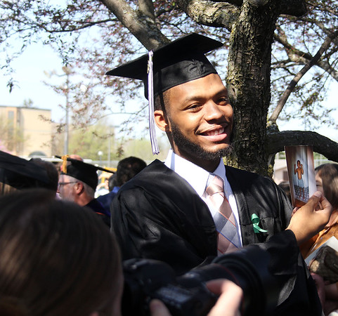 STEPHEN BROOKS   THE GOSHEN NEWS<br /> Goshen College graduating senior Dominique Bolden smiles while holding up a baby photo included in a card from family members after Sunday's commencement ceremony.