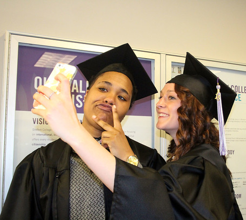 SHERRY VAN ARSDALL | THE GOSHEN NEWS<br /> At left, Jomani Thomas, Fort Wayne, and Liz Tecca, Kalamazoo, Mich., take a selfie before the processional of the 118th Goshen College Commencement Sunday. Thomas majored in physical education and Tecca majored in business.