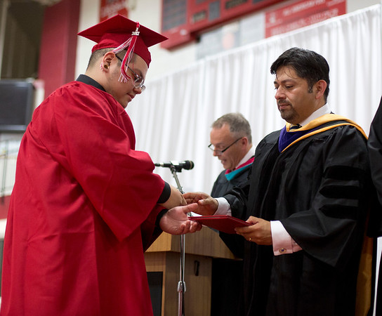 JAY YOUNG | THE GOSHEN NEWS<br /> Goshen High School graduating senior Roberto Hernandez, Jr. receives a handshake and his diploma from board of education president Felipe Merino during the 2017 Commencement ceremony Sunday afternoon.