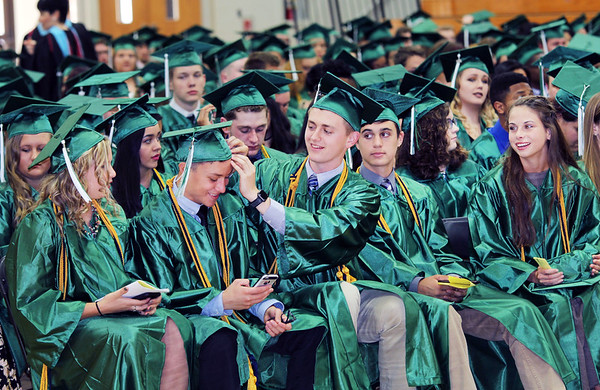 JOHN KLINE | THE GOSHEN NEWS <br /> Concord High School senior Noah Nisen, center, adjusts the cap of fellow senior Bezner Gomez prior to the start of the 2017 commencement ceremony at the high school Thursday evening. There were a total of 366 graduates in Concord's 2017 graduating class. Named as Valedictorian for the class of 2017 was Lauren Boone. Allyse Smith was named Salutatorian. Serving as the invited faculty speaker at this year's graduation ceremony was Concord High School Social Studies teacher Dan Ross.