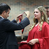 JULIE CROTHERS BEER | THE GOSHEN NEWS<br /> Senior class sponsor Mike Nolt, at left, prepares to place a medal around the neck of NorthWood High School graduate Sara Bowling as students prepared for the graduation ceremony Friday night.