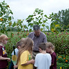 HALEY WARD | THE GOSHEN NEWS<br /> Bill Weybright hands second graders from Benton Elementary sunflowers seeds to take home from his garden during field trip Thursday at the garden at Greencroft Communities. Weybright is a Greencroft resident and planted the patch of flowers that also include marigolds and zinnias.