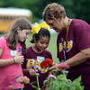 HALEY WARD | THE GOSHEN NEWS<br /> Second graders Lacey Stoltzfus, Raquel Guevara and their teacher Peggy Fisher look at a zinnia during a Benton Elementary School field trip Thursday at the garden at Greencroft Communities.