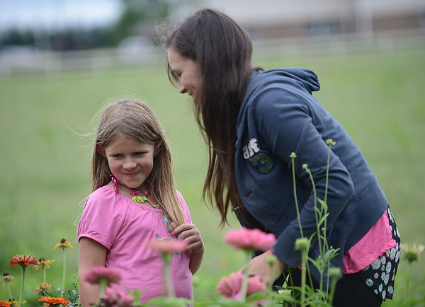HALEY WARD | THE GOSHEN NEWS<br /> Second grader Kylee Orr and her mom Tracy admire the zinnias during a Benton Elementary School field trip Thursday at the garden at Greencroft Communities. The students toured their butterfly garden and the other flowers for their science inquiry unit. The students also have plans to grow their own butterfly garden at their school.