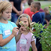 HALEY WARD | THE GOSHEN NEWS<br /> Second graders Madison Jones and Lexi Jacobs look at a flower during a Benton Elementary School field trip Thursday at the garden at Greencroft Communities.