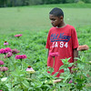 HALEY WARD | THE GOSHEN NEWS<br /> Second grader Jayden Zamora admires the flowers during a Benton Elementary School field trip Thursday at the garden at Greencroft Communities.