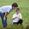 HALEY WARD | THE GOSHEN NEWS<br /> Second graders Christian Densmore and Tyler Miller look at marigolds during a Benton Elementary School field trip Thursday at the garden at Greencroft Communities.