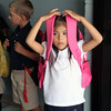 JULIE CROTHERS | THE GOSHEN NEWS<br /> Bianca Macias, 6, holds her backpack over her head Thursday as she waits to be picked up after her first day of first grade at St. John the Evangelist Catholic School.