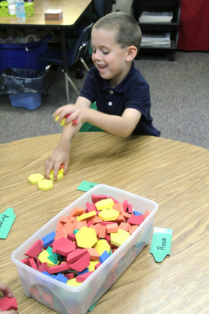 JULIE CROTHERS   THE GOSHEN NEWS<br /> Liam Post, 5, collects a pile of foam shapes Thursday during his first day of kindergarten at St. John the Evangelist Catholic School.