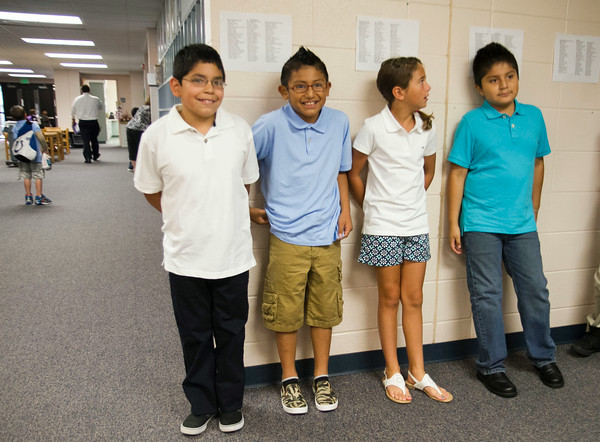 SAM HOUSEHOLDER   THE GOSHEN NEWS<br /> West Goshen Elementary fourth grade students Oswaldo Gamboa, Eduardo Gonzalez, Addison Schade and Hector Juarez stand in line with their class Thursday morning. Thursday was the first day of school and the first day for the school's new dress code, which requires polo shirts like those the students are seen wearing.