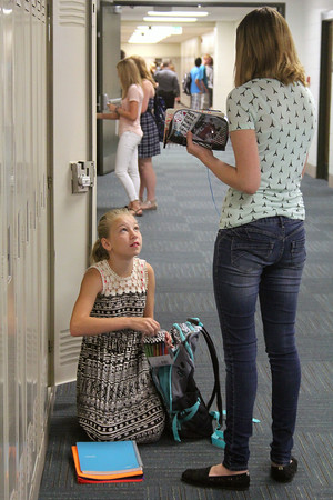 JULIE CROTHERS | THE GOSHEN NEWS<br /> Freshman Reagon Dailey removes a pencil from her backpack while talking with classmate Nataleigh Friedrich before the first day of school Tuesday at Wawasee High School.