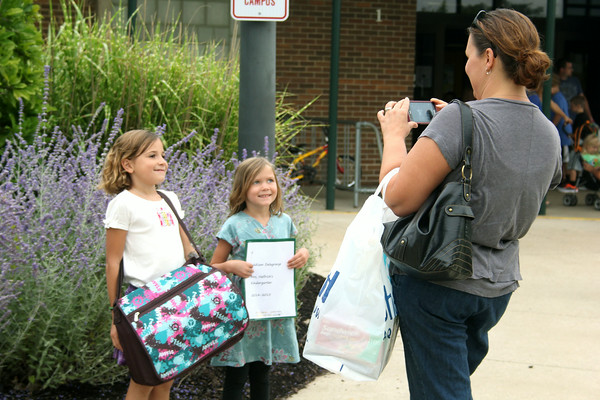 JULIE CROTHERS | THE GOSHEN NEWS<br /> Sisters Delaney and Addison Delagrange pose for a photo taken by mom Celia Delagrange in front of Syracuse Elementary School on the first day of school. Delaney is a third grader and Addison began her first day of kindergarten on Tuesday.