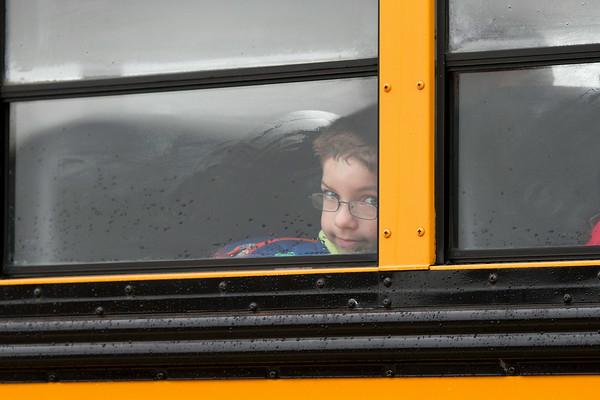 SAM HOUSEHOLDER   THE GOSHEN NEWS<br /> Zander Thibos peeks out the window of a school bus outside Shipshewana Scott Elementary School Tuesday. Thibos is starting the second grade.