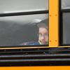 SAM HOUSEHOLDER | THE GOSHEN NEWS<br /> Zander Thibos peeks out the window of a school bus outside Shipshewana Scott Elementary School Tuesday. Thibos is starting the second grade.