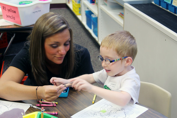 JULIE CROTHERS | THE GOSHEN NEWS<br /> Kindergarten teacher Carrie Johnson talks with Lennon Geyer as he searches for the right color crayon to complete his picture. Nappanee Elementary School students returned to class Thursday.