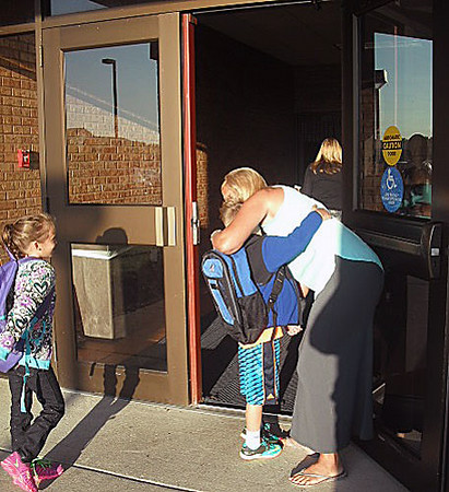 AMY WENGER | THE GOSHEN NEWS<br /> Wakarusa Elementary schoolteacher Laurie Frantz gives a young student a warm hug upon his return to classes at the start of the 2014-15 school year on Thursday.