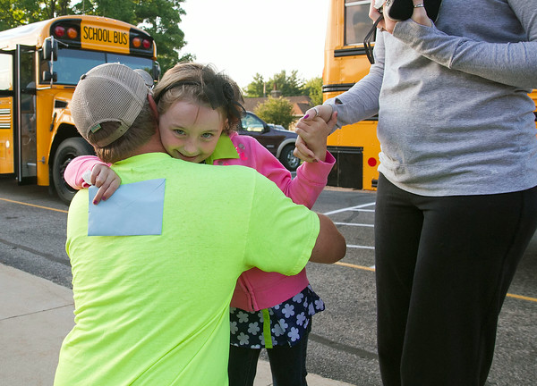 SAM HOUSEHOLDER | THE GOSHEN NEWS<br /> Layla Porter hugs her stepfather Todd Truex Thursday before her first day of kindergarten at Millersburg Elementary School. Fairfield Community Schools began the 2014-2015 school year Thursday.
