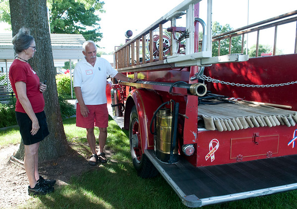 HALEY WARD | THE GOSHEN NEWS<br /> Bob Elliott shows off his 1935 firetruck to Fritzie Ridenoure during the Goshen High School Alumni Reunion on Sept. 1 at the Elkhart County 4-H Fairgrounds. The two graduated from GHS in 1962.