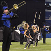 SAM HOUSEHOLDER | THE GOSHEN NEWS<br /> T.J. Jensen, left, plays while color guaard members Sophie Hochstetler, center and Chantell Martin throw sabers in the air during the ISSMA State Marching Band Finals in Indianapolis Saturday.