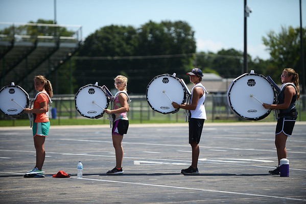 HALEY WARD | THE GOSHEN NEWS <br /> The bass drums junior Camille Lozier, senior Alexis Keeley, sophomore Clayton Greer and sophomore Courtney Barr warm up during marching band practice at Concord High School.