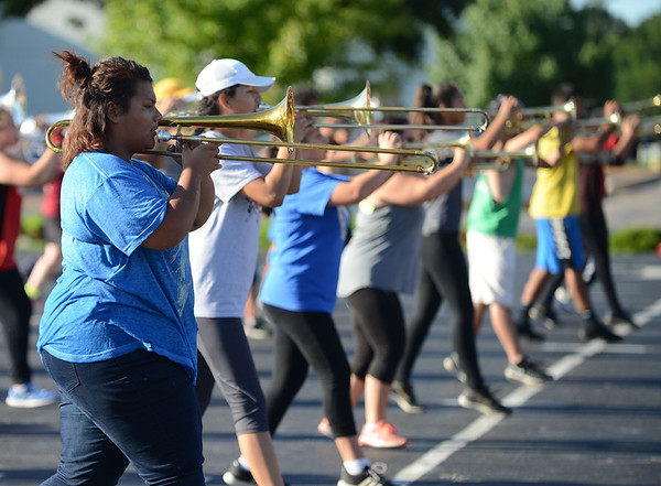 HALEY WARD | THE GOSHEN NEWS<br /> Lupita Romo and Katja Gutierrez practice their marching with their trombones during the Crimson Marching Band rehearsal Thursday at Goshen High School.