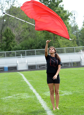 HALEY WARD | THE GOSHEN NEWS<br /> Freshman Arline Guillen tosses her flag during the Marching Chargers' rehearsal Tuesday at NorthWood High School.