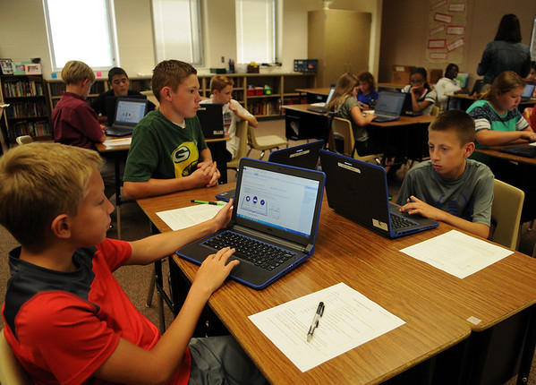 HALEY WARD | THE GOSHEN NEWS<br /> Seventh graders Ashton Beachy, Zack Gibson and Quentin Fisher set up their computers in their language arts class Monday at NorthWood Middle School.