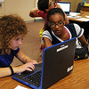 HALEY WARD | THE GOSHEN NEWS<br /> Fatima Ghaffar helps Morgan Jenkins set up her Microsoft OneNote in the seventh-grade language arts class Monday at NorthWood Middle School.