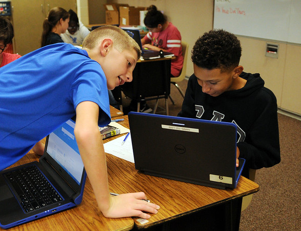 HALEY WARD | THE GOSHEN NEWS<br /> Tanner Hostetler looks over to Armani Kimbrough's computer in their seventh-grade language arts class Monday at Northwood Middle School.