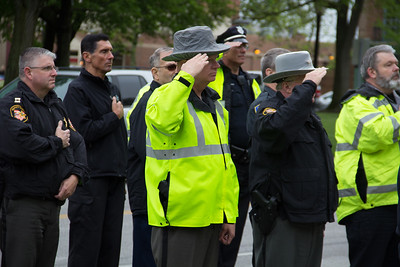 ALEC SMITH / GAZETTE Capt. Ken Baca of the Medina County Sheriff's Office (center) and Sheriff Tom Miller (right) salute the flag during the playing of the national anthem on Saturday at a rally on Public Square in Medina to support the work of law enforcement.