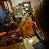 "KRISTOPHER RADDER — BRATTLEBORO REFORMER<br /> Deborah Lazar, of Putney, uses various shades of orange to work on a painting of Brattleboro Select Board Member Shanta Lee Gander during a portrait series ""Secret Lives of Shopkeepers"" at the River Gallery on Thursday, Oct. 4, 2018."