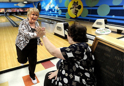 Sue Klemoff, 62, left, gets a high-five from her friend Margie Sommers, 71, after bowling a strike during a senior bowling league on Monday, Oct. 15, at Chipper Lanes in Broomfield. For more photos and video of the bowling league go to www.dailycamera.com  Jeremy Papasso/ Camera