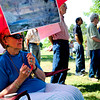 "Nancy St. Germain, a resident of Frasier Meadows Retirement Community listens to speakers under an umbrella displaying photos she took of Thunderbird lake. Members of Frasier Meadows held a senior sit-in at Admiral Arleigh A Burke Park Friday morning in order to protest against the city's plan to let the lake return to it's natural level. August 10, 2012. Rachel Woolf/ For the Daily Camera. For more photos and a video of the sit-in, go to  <a href=""http://www.dailycamera.com"">http://www.dailycamera.com</a>."