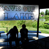 "From left, David Chiszar, of Boulder and his son Adam Chiszar, of Denver, sit under a ""Save Our Lake"" sign. Members of Frasier Meadows Retirement Community held a senior sit-in at Admiral Arleigh A Burke Park Friday morning in order to protest against the city's plan to let the lake return to it's natural level. August 10, 2012. Rachel Woolf/ For the Daily Camera. For more photos and a video of the sit-in, go to  <a href=""http://www.dailycamera.com"">http://www.dailycamera.com</a>."